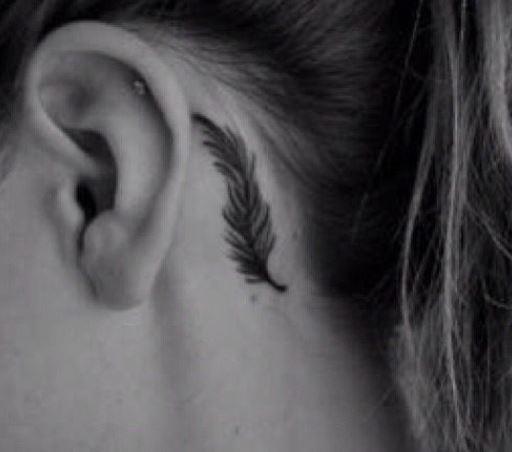 Piccolo tatuaggio femminile di piuma dietro orecchio